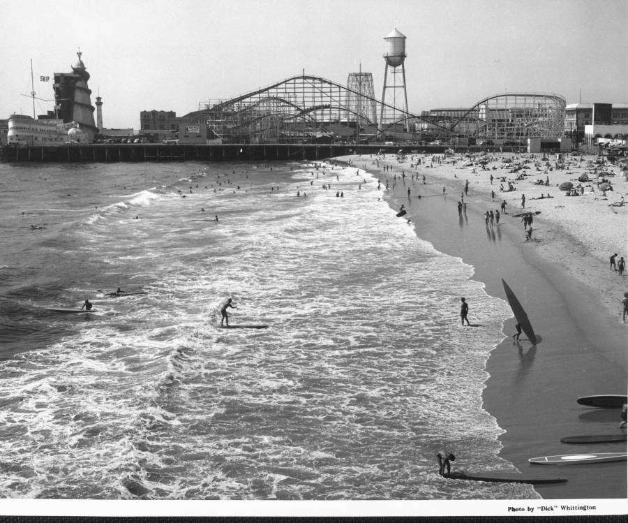 1939 - People crowd the beach next to an amusement park