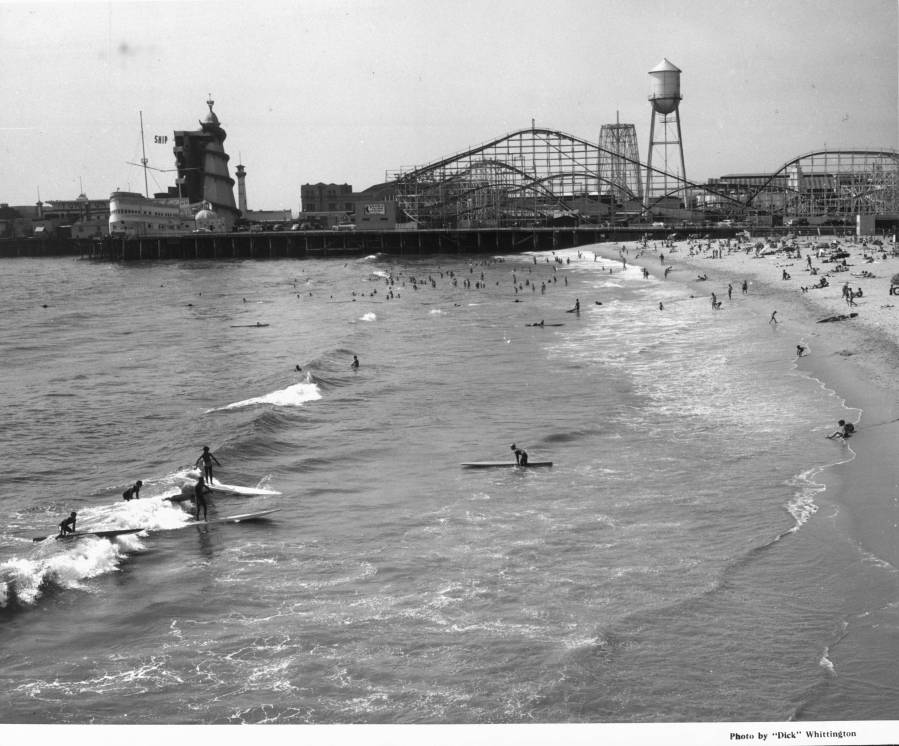 1939 - Surfers ride waves at a crowded beach
