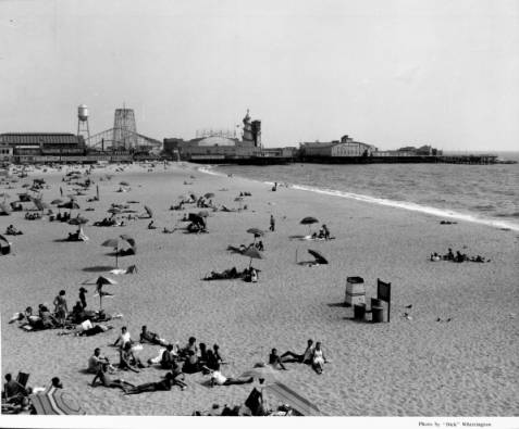 1939 - People relax on the beach in the sun and under umbrellas