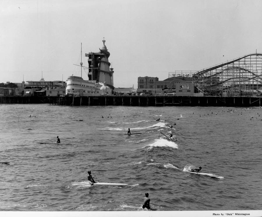 1939 - People ride surf boards and paddle boards in front of an amusement park