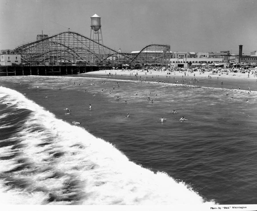 1939 - People swimming at a beach await the arrival of a large wave