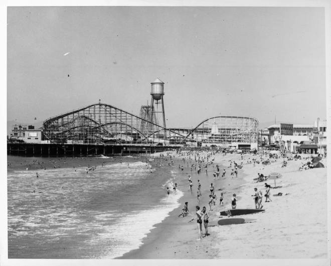 1940 - People frolic on the beach near the roller coaster in the amusement park at Venice Beach