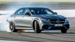 A photo of the 2017 Mercedes-AMG E 63 S 4Matic+ on a test track. The vehicle is smoking its tires as it oversteers through a turn.