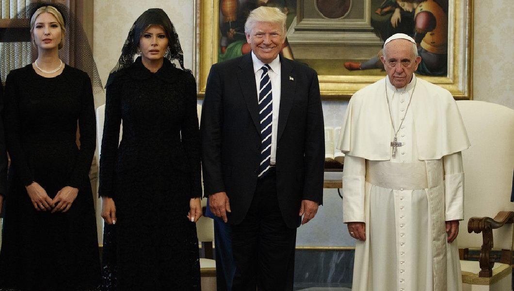A photograph of Ivanka, Melania, and the Donald meeting with Pope Francis. Ivanka and Melania wear dour expressions on their faces, while Donny is grinning ear to ear.
