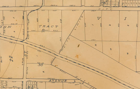 A 1910 City Map. A rail line arcs from the middle of the left to the bottom right corner. There is a rail junction as well. The map shows city streets, and tracts of undeveloped farm land.